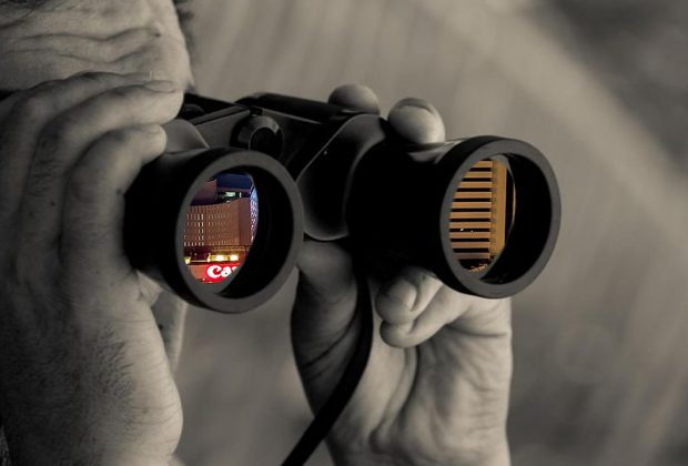 find missing persons Thailand, an investigator looking through binoculars